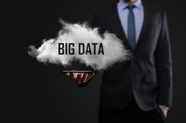 Hand, die eine wolke mit den wörtern big data auf dunkler oberfläche zeigt