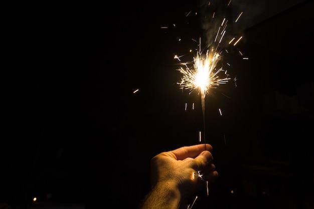 Hand, die eine wunderkerze in der nacht für diwali hindu festival der lichter in mysore, karnataka, indien hält. hinduismus religion feier konzept