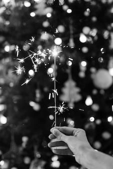 Hand, die eine wunderkerze mit einem weihnachtsbaum in schwarzweiss hält