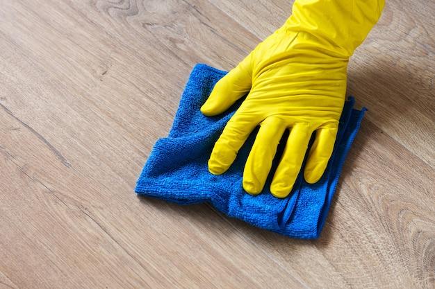 Hand, die einen gelben gummihandschuh trägt und einen laminatboden mit einem blauen nassen tuch wäscht