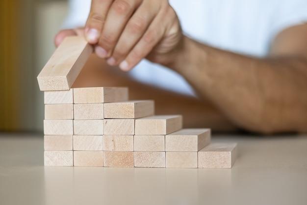 Hand, die einen hölzernen stapelblock wie eine stufenleiter auf einem holztisch anordnet. geschäftskonzept für einen erfolgreichen wachstumsprozess. platz kopieren