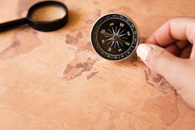 Hand, die einen kompass auf einer karte hält