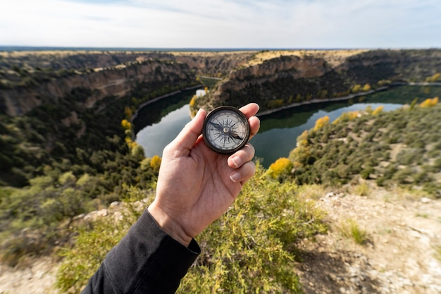 Hand, die einen kompass hält, auf einer klippe mit einem fluss, reisekonzept,