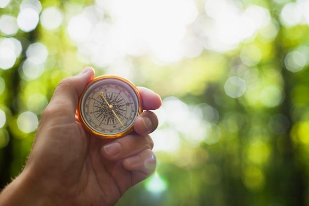 Hand, die einen kompass mit unscharfem hintergrund hält