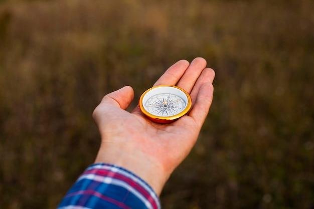 Hand, die einen kompass mit unscharfem hintergrund zeigt