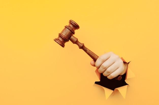 Hand, die einen richterhammer durch zerrissenes gelbes papierwandgesetz und gerichtstriumph der gerechtigkeit hält