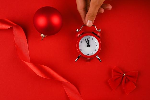 Hand, die einen roten wecker auf rotem hintergrund mit weihnachtselementen hält.