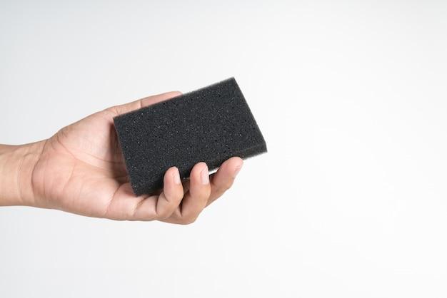 Hand, die einen schwarzen reinigungsschwamm hält