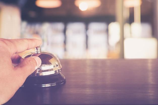 Hand, die einen service bell-anrufservice auf hotelrezeptions-abschluss oben drückt