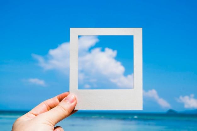 Hand, die einen sofortigen fotorahmen gegen blauen himmel anhält