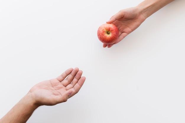 Hand, die einer bedürftigen person einen apfel gibt