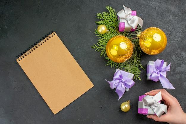 Hand, die eines von bunten geschenken und dekorationszubehör und notizbuch auf dunklem hintergrund hält