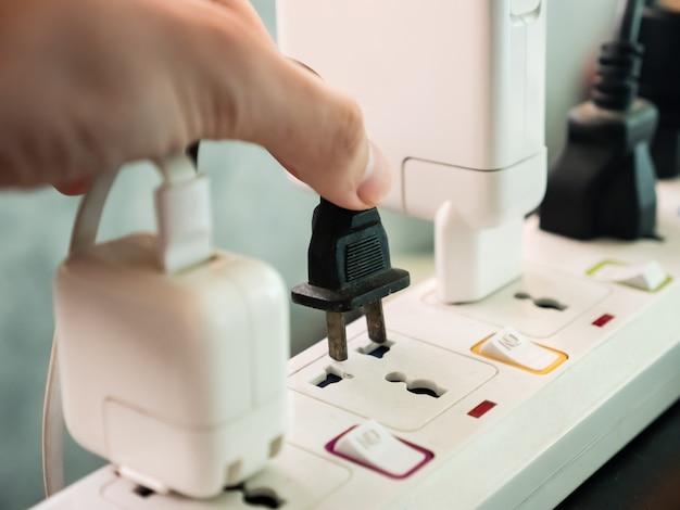 Hand, die elektrischen stecker hält