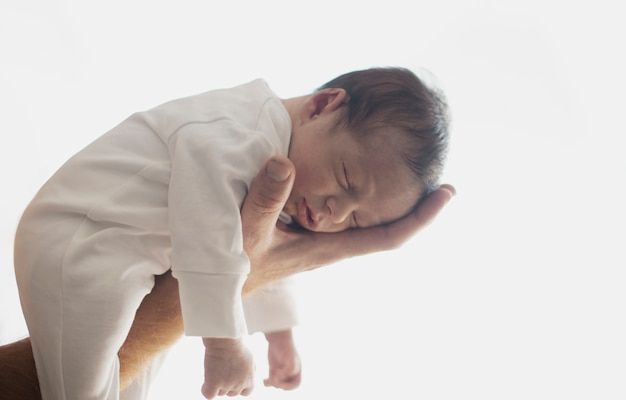 Hand, die entzückendes neugeborenes hält