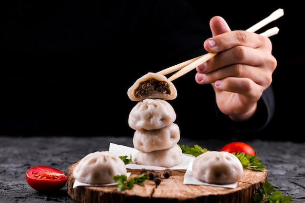 Hand, die essstäbchen mit mehlkloß hält