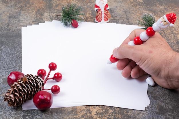 Hand, die etwas mit schönem bleistift auf blatt papier schreibt
