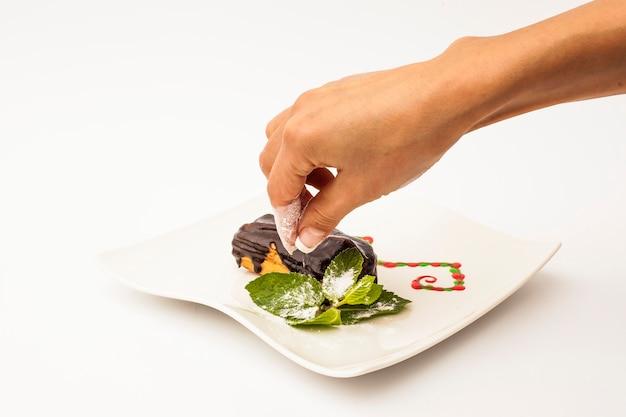 Hand, die etwas zucker auf eclair-kuchen mit schokolade auf weißem teller mit einer minze auf einem weißen hintergrund setzt.