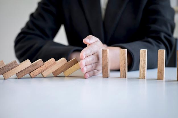 Hand, die fallenden zusammenbruchholzklotz-dominoeffekt vom ununterbrochenen gestürzten block stoppt