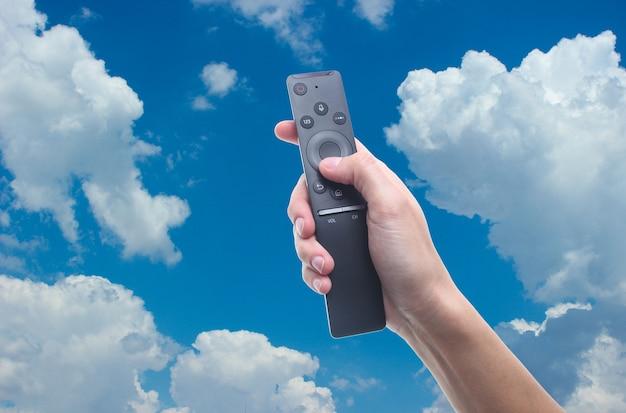 Hand, die fernbedienung gegen blauen himmel mit weißen wolken hält