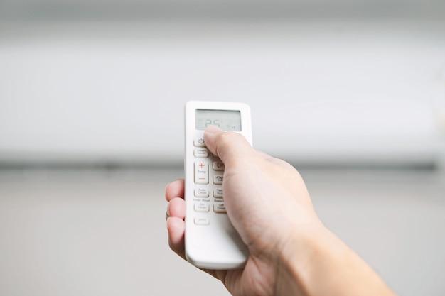 Hand, die fernbedienung hält, um temperatur der klimaanlage einzustellen.