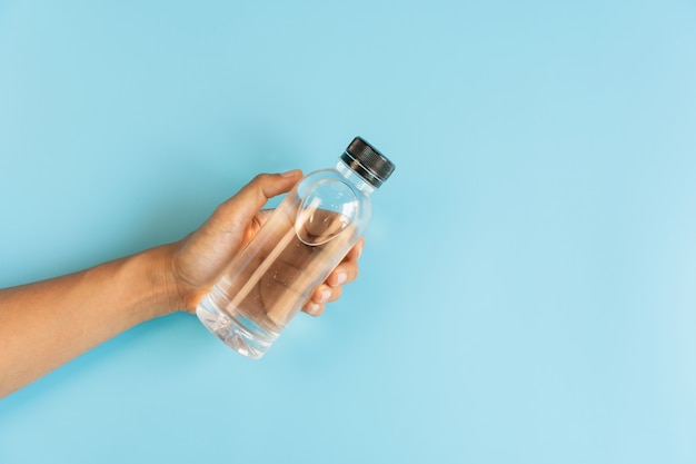 Hand, die flasche mineralwasser auf blau hält