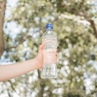 Hand, die flasche wasser hält