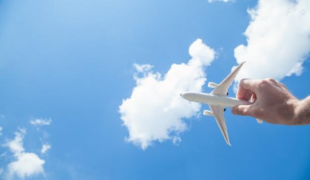 Hand, die flugzeugmodell vor blauem himmelhintergrund hält. reise