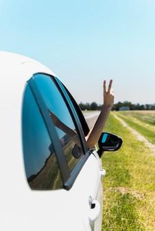 Hand, die Friedenszeichen durch Autofenster macht