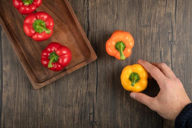 Hand, die frischen roten paprika auf holzoberfläche hält