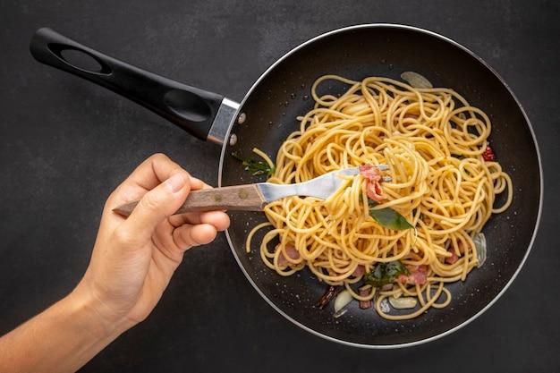 Hand, die gabel hält spaghetti-nudeln mit getrocknetem chili, knoblauch, süßem basilikum und speck in schwarzer pfanne auf dunklem texturhintergrund, draufsicht