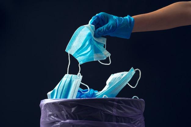 Hand, die gebrauchte schmutzige chirurgische maske auf eine mülltonne legt.
