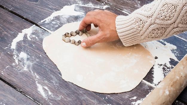 Hand, die geformte plätzchen des weihnachtsbaums schneidet
