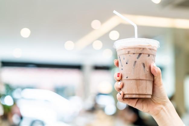 Hand, die gefrorene belgische schokoladenmilchshaketasse hält