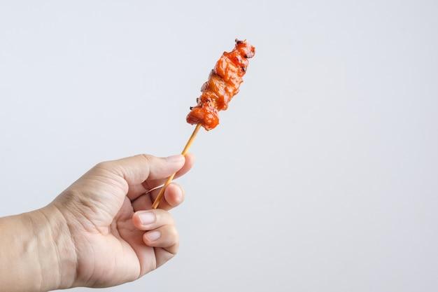 Hand, die gegrilltes hühnerfleisch, eine asiatische lebensmittelaufsteckspindel hält
