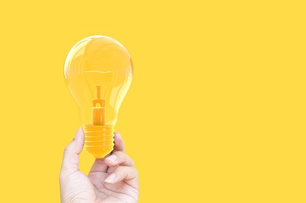 Hand, die gelbe pastellfarbe der glühlampe hält