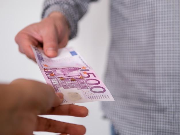 Hand, die geld- banknote des euros 500 gibt.