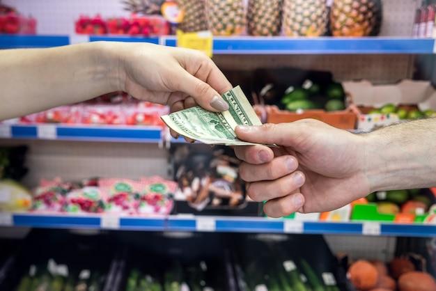 Hand, die geld im supermarkt übergibt. kaufkonzept
