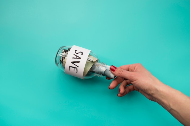 Hand, die geld in glas legt