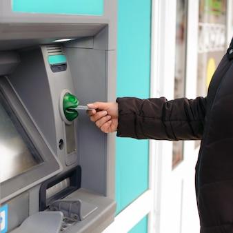 Hand, die geldautomatenkarte in bankautomaten einführt, um geld abzuheben