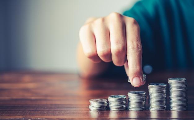 Hand, die geldmünze auf jede steigende linie setzt - geschäftssparendes geldkonzept für die finanzbuchhaltung