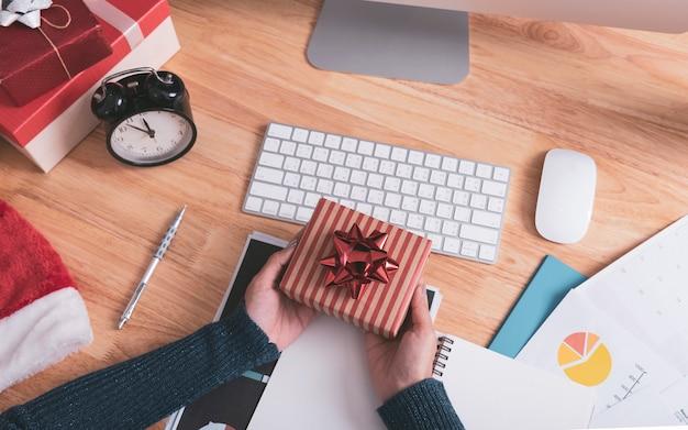 Hand, die geschenkbox in den weihnachtsfeiertagen im büro mit weihnachtsdekoration auf tabelle hält.