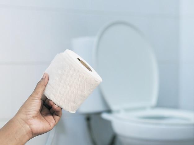 Hand, die gewebe über verschwommenem weißem toilettenhintergrund hält.