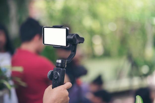 Hand, die gimbal mit smartphoneaufzeichnungsvideo hält