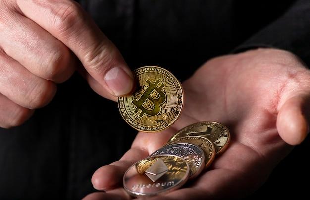 Hand, die glänzende goldbitcoin mit anderer kryptowährung in männlicher hand auf schwarzem hintergrund in die handfläche legt, nahaufnahme.