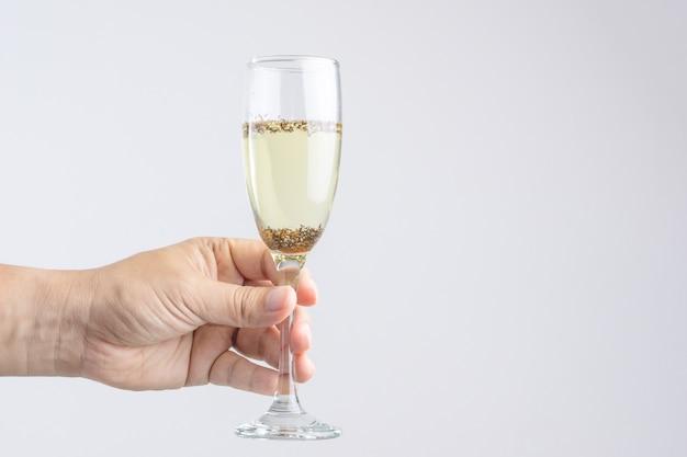 Hand, die glas champagner mit plage oder insekt hält