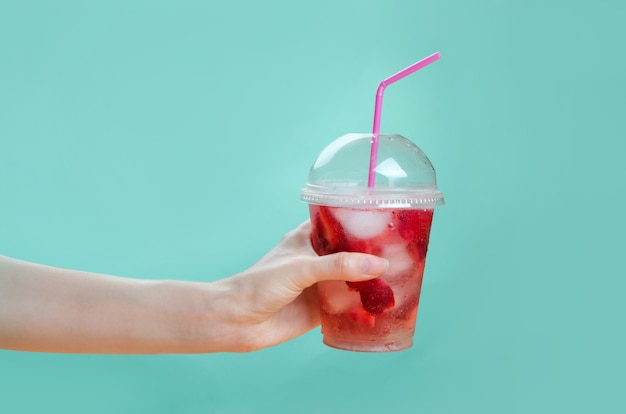Hand, die glas des erdbeercocktails auf rosa und grünem hintergrund hält