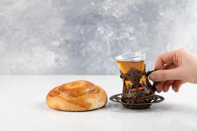 Hand, die glas des schwarzen tees auf einer weißen oberfläche hält