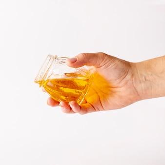 Hand, die glas mit honig hält