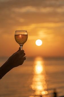 Hand, die glas wein gegen einen schönen sonnenuntergang nahe meer am tropischen strand hält
