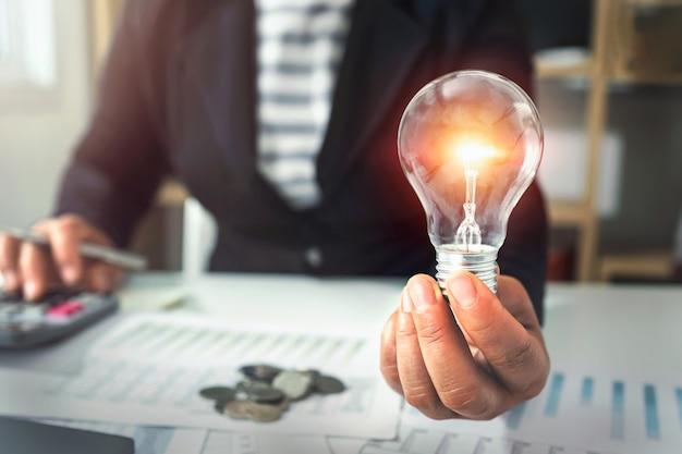 Hand, die glühbirne hält. ideenkonzept mit innovation und inspiration